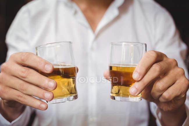 Крупный холдинг виски бармен выстрел очки барной стойкой в баре — стоковое фото