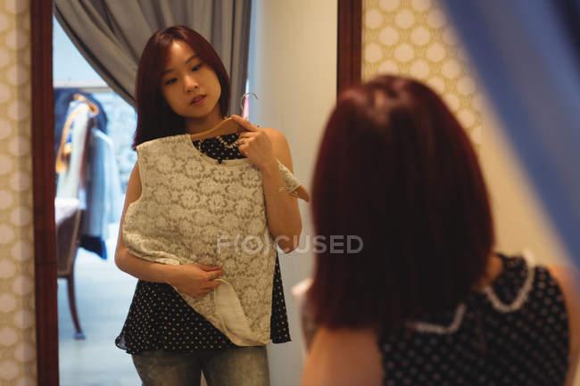 Mujer mirando el espejo mientras intenta una parte superior en la tienda boutique - foto de stock