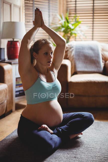 Красивая беременная женщина, занимающаяся йогой в гостиной дома — стоковое фото