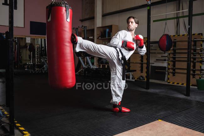 Schöner Mann übt Karate mit Boxsack im Fitnessstudio — Stockfoto