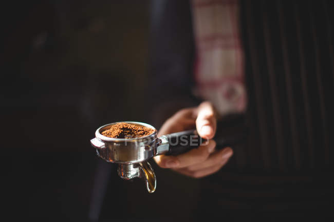 Mid section of waiter holding portafilter filled with ground coffee in cafe — Stock Photo
