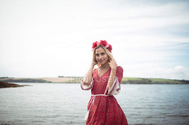 Carefree blonde woman wearing flower tiara and standing near river — Stock Photo