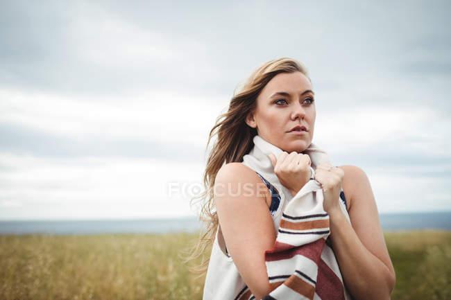 Femme debout dans le champ lors de temps venteux — Photo de stock