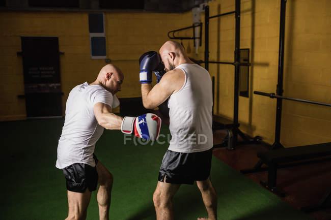 Seitenansicht zweier thailändischer Boxer, die im Fitnessstudio boxen — Stockfoto
