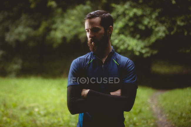 Athlete standing with arms crossed in forest — Stock Photo