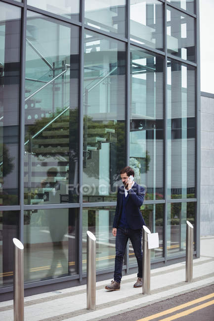 Businessman talking on mobile phone while walking on footpath — Stock Photo