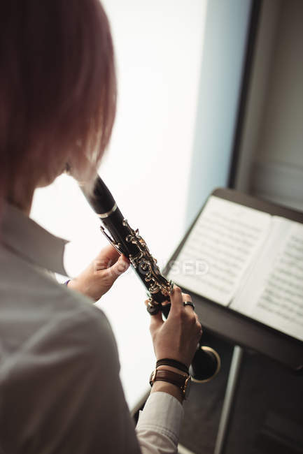 Aufmerksame Frau spielt Klarinette in Musikschule — Stockfoto