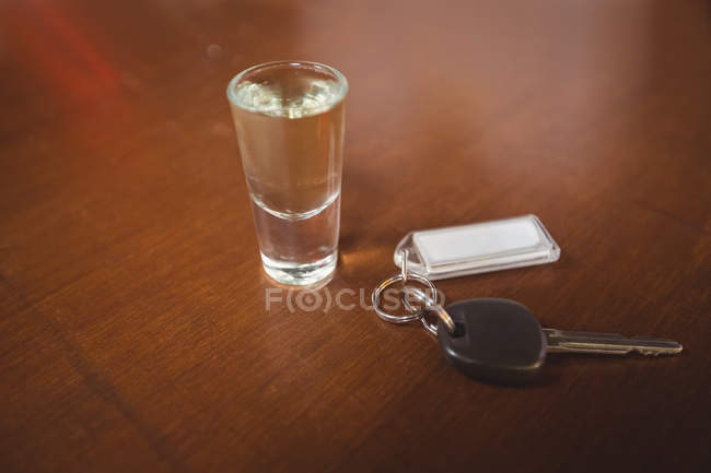 Glass of tequila shot with car key in bar counter at bar — Stock Photo