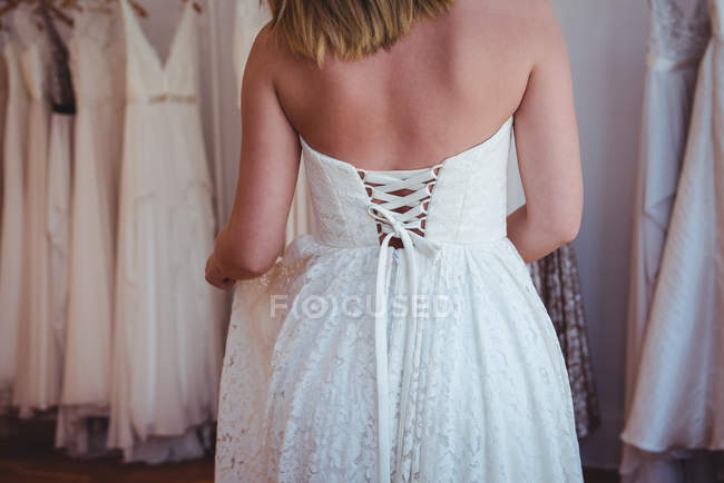 Schöne Frau probiert Hochzeitskleid in einem Geschäft im Atelier an — Stockfoto