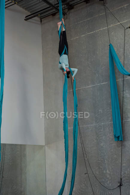 Gymnast exercising on blue fabric rope in fitness studio — Stock Photo