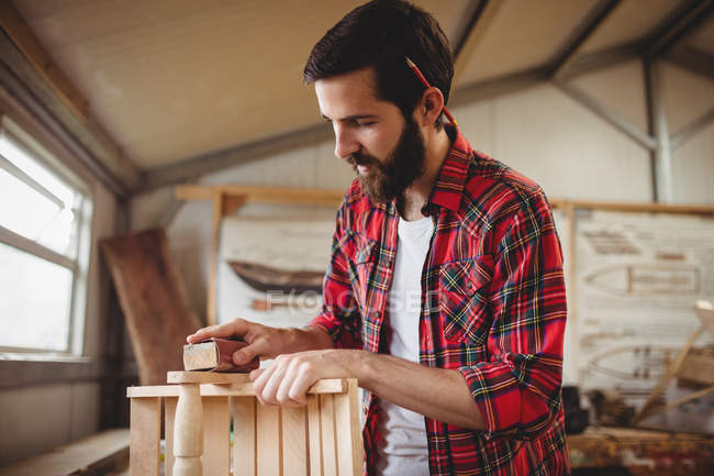 Man working over a wooden plank at boatyard — Stock Photo