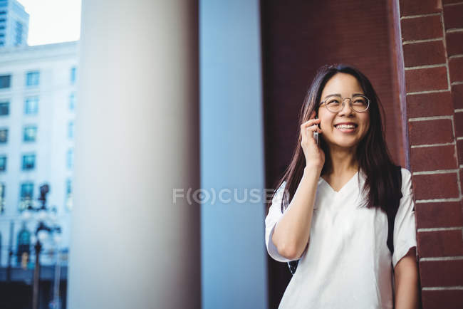 Woman talking on mobile phone in passage — Stock Photo