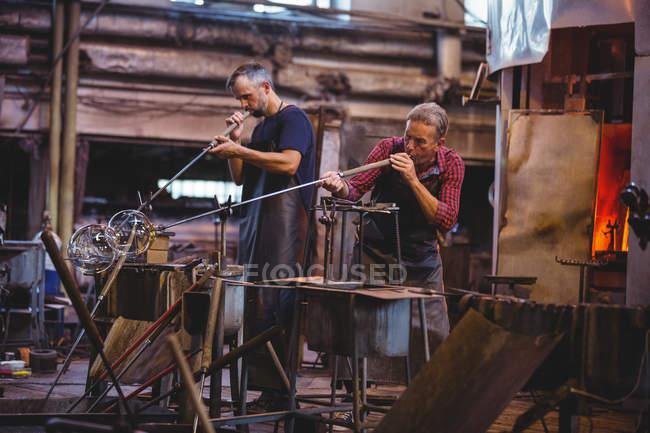 Glassblowers формування скла на blowpipes заводі glassblowing — стокове фото