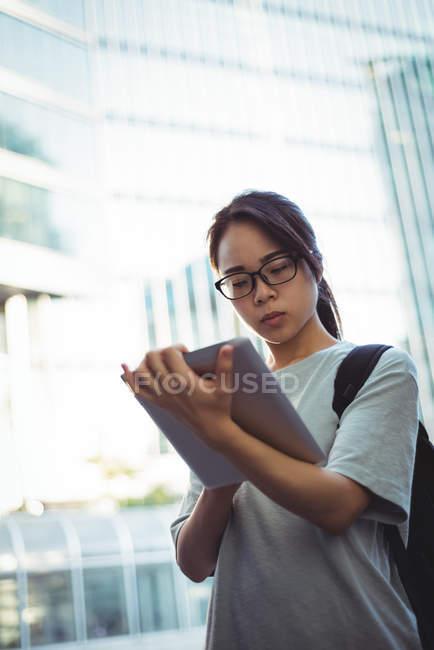 Молода жінка, використовуючи цифровий планшет на вулиці — стокове фото