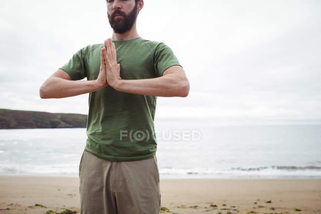 Homem realizando ioga na praia — Fotografia de Stock