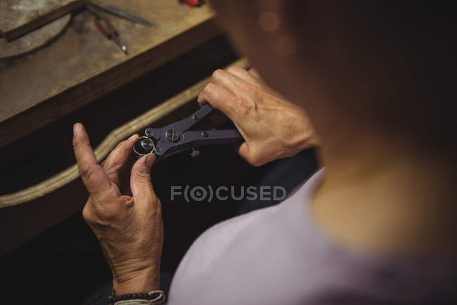 Hands of craftswoman using pliers in workshop — Stock Photo