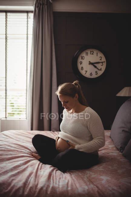 Mujer embarazada relajándose en el dormitorio en casa - foto de stock