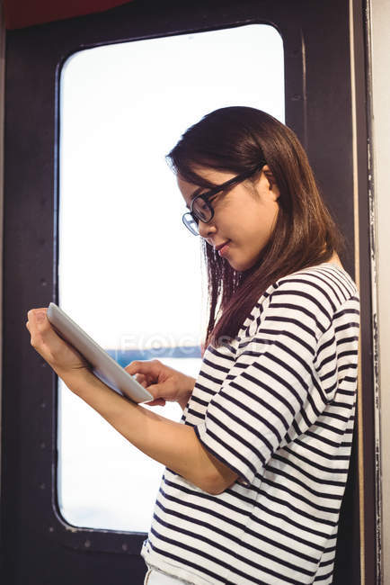 Young woman leaning on wall while using digital tablet — Stock Photo
