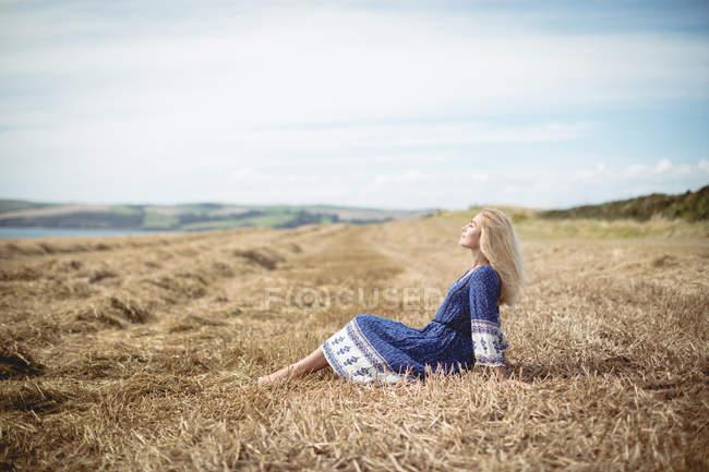 Vista lateral da mulher loira atraente sentado em campo — Fotografia de Stock