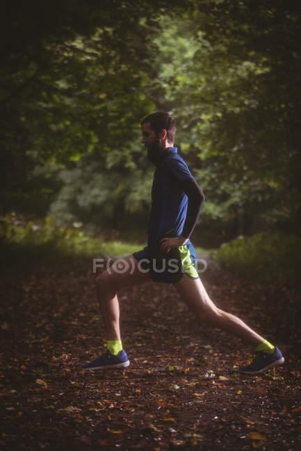 Спортсмен виконує розтяжку Вправа в лісі — стокове фото