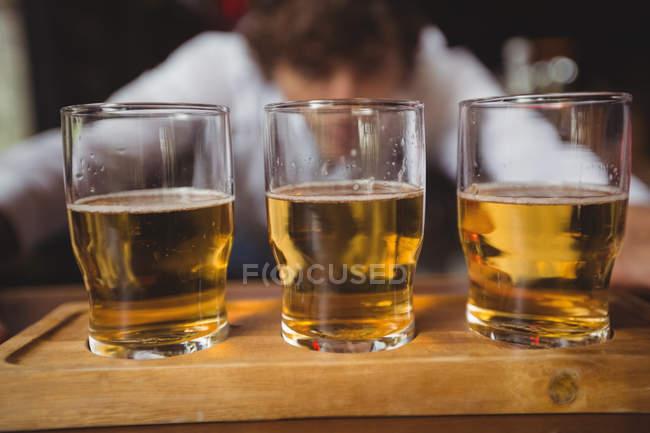 Bartender lining whisky shot glasses on bar counter at bar — Stock Photo