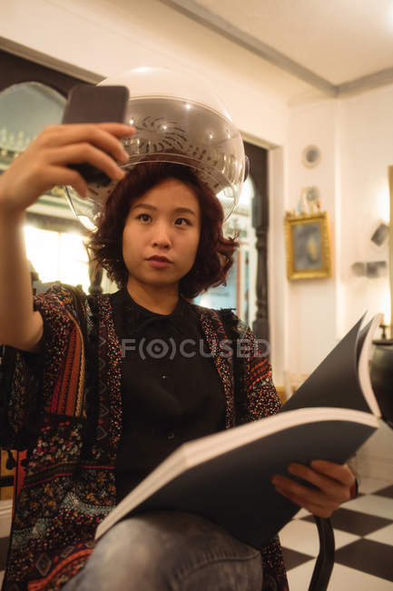 Stylish woman taking a selfie while sitting under a hairdryer at hair salon — Stock Photo