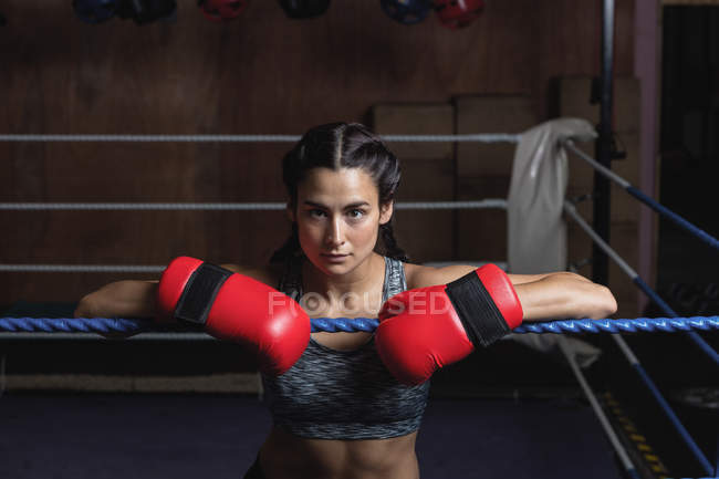 Tired female boxer in boxing gloves leaning on ropes of boxing ring at fitness studio — Stock Photo