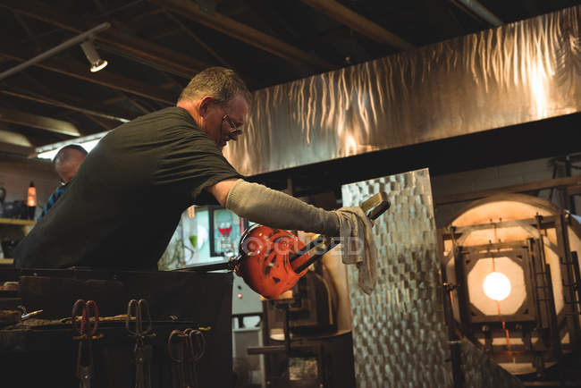 Glassblowers shaping molten glass at glassblowing factory — Stock Photo