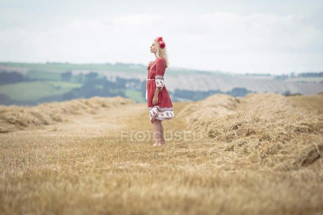 Vista lateral de la mujer rubia despreocupada de pie en el campo - foto de stock