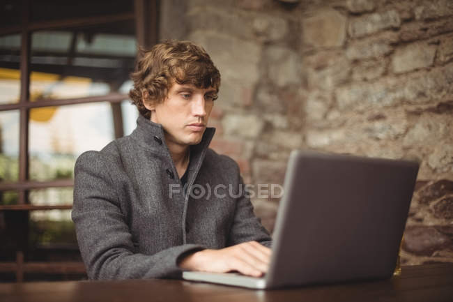 Man using laptop at bar — Stock Photo