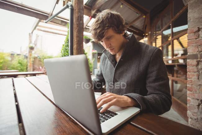 Hombre usando el ordenador portátil en el bar - foto de stock