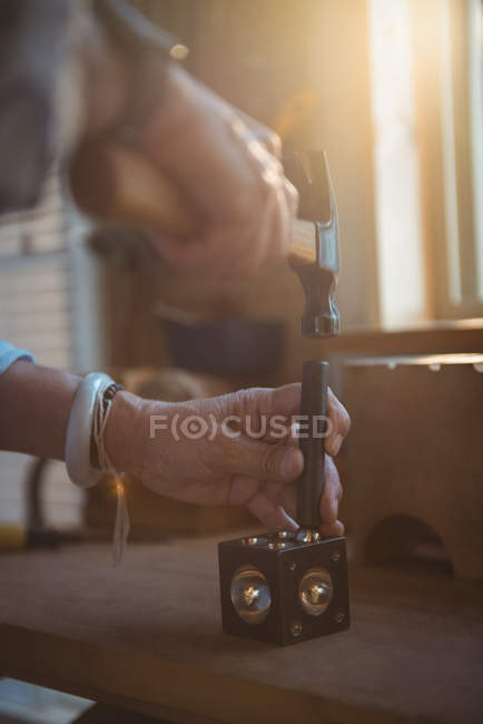 Hands of craftswoman using hammer in workshop — Stock Photo