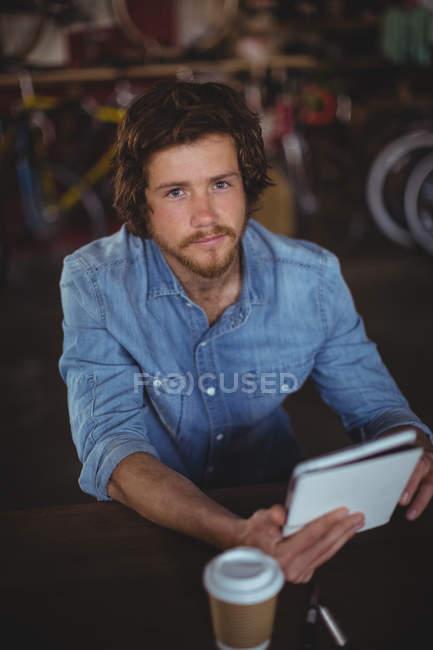 Portrait of handsome mechanic using digital tablet in workshop — Stock Photo