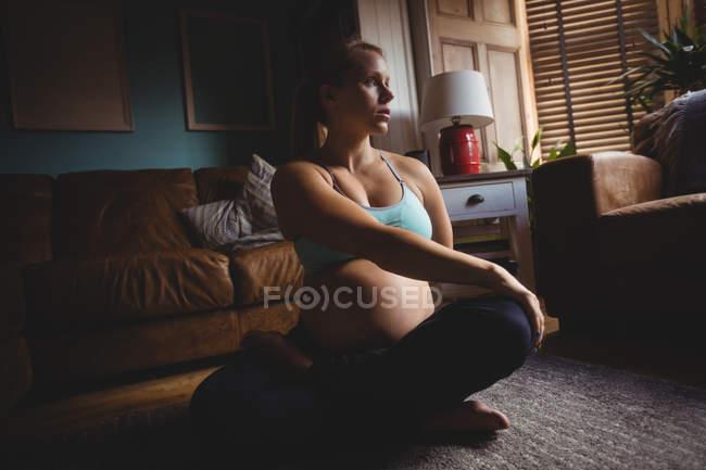 Беременная женщина растягивается в гостиной дома — стоковое фото