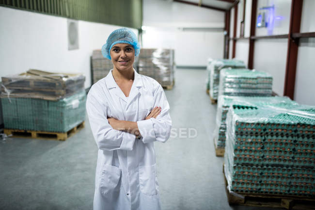 Portrait of female staff standing with arms crossed in egg factory — Stock Photo