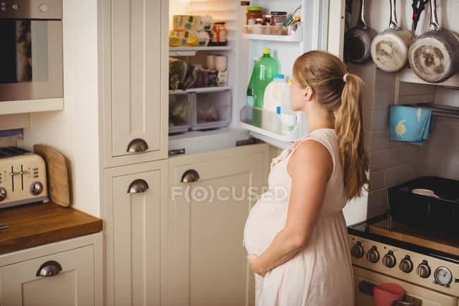Беременная женщина ищет еду в холодильнике на кухне — стоковое фото