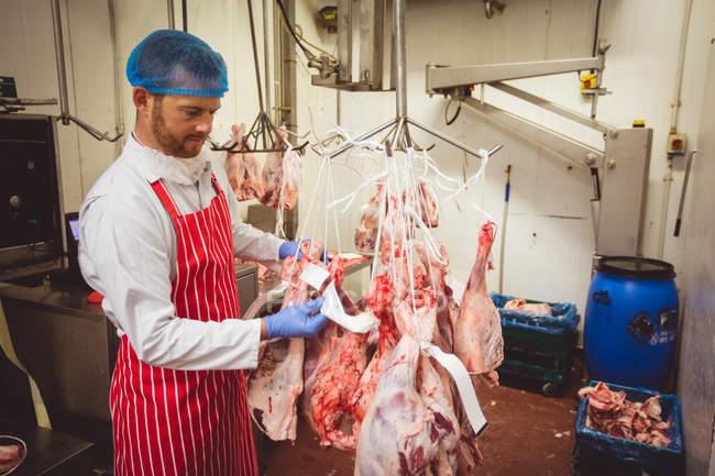 Мясник наклеивает наклейки со штрих-кодами на красное мясо на складе мясной лавки — стоковое фото