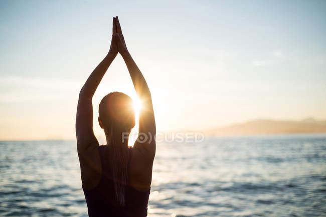 Задний вид женщины, практикующей йогу на пляже во время заката — стоковое фото