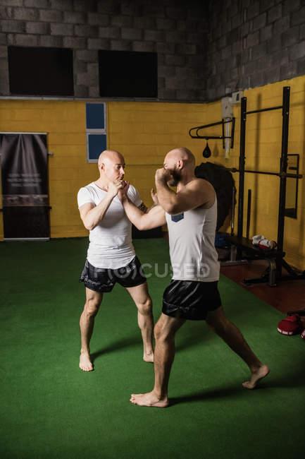 Pleine longueur de deux boxeurs thaïlandais pratiquant la boxe dans la salle de gym — Photo de stock