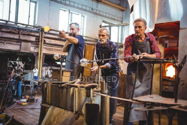 Команда glassblowers формування скла на blowpipes заводі glassblowing — стокове фото