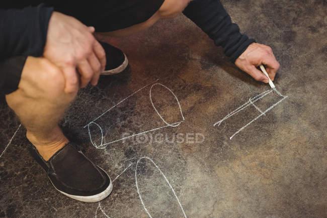 Обрезанное изображение диаграммы рисунка стеклодува на полу на стекольном заводе — стоковое фото