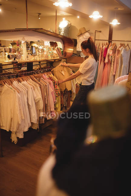 Woman selecting clothes on hangers at apparel store — Stock Photo