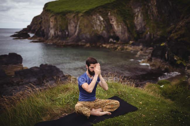 Homme effectuant le yoga sur la falaise — Photo de stock