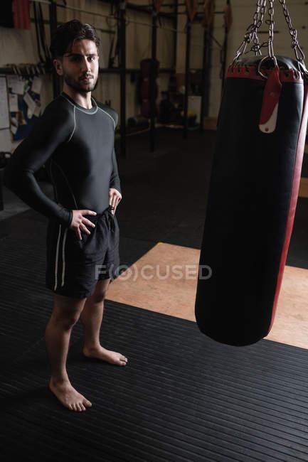 Портрет боксера, стоящего с руками на бедрах рядом с боксерской грушей в фитнес-студии — стоковое фото
