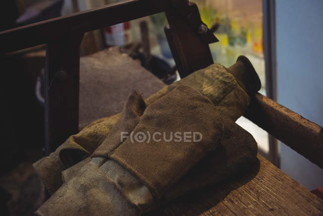 Close-up of glassblowing gloves on table at glassblowing factory — Stock Photo