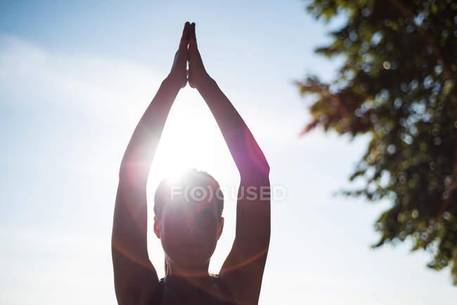 Женщина практикует йогу в саду в солнечный день — стоковое фото