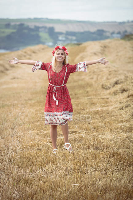 Happy Carefree blonde woman standing in field with arms spread — Stock Photo