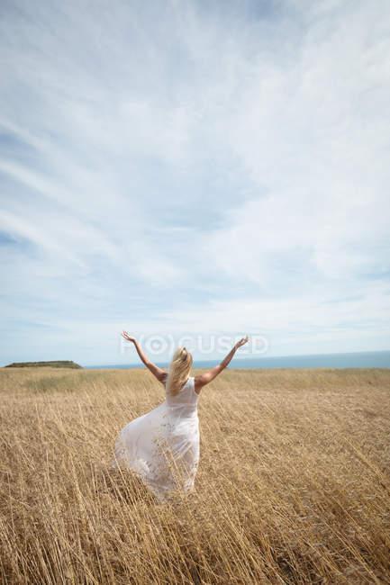 Vue arrière de la femme blonde debout dans le champ avec les bras ouverts — Photo de stock