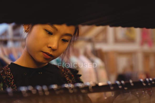 Femme en sélectionnant des vêtements sur cintres à vêtements magasin — Photo de stock