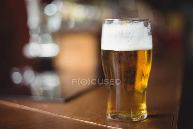 Glass of beer in counter at bar — Stock Photo
